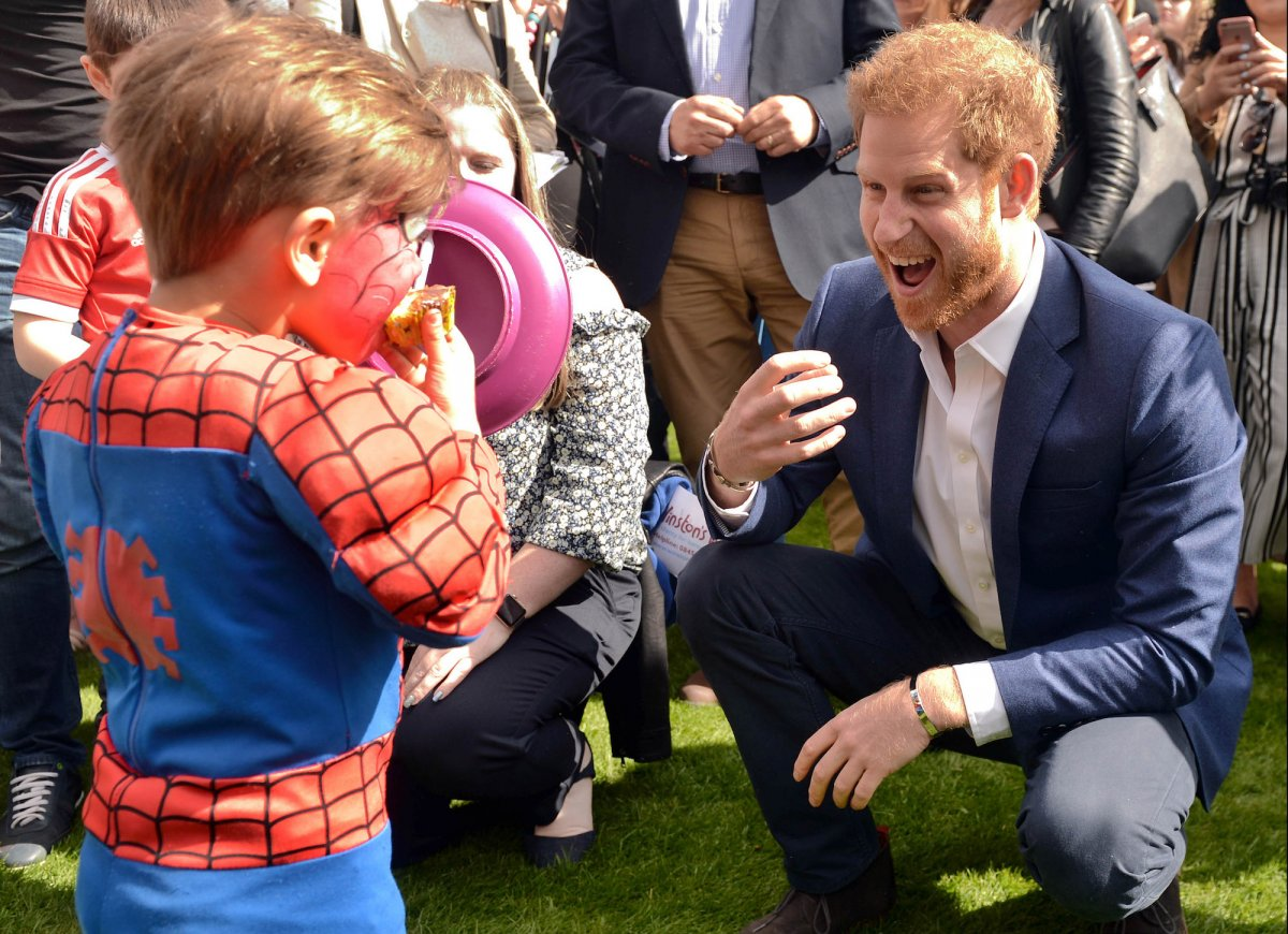 Summer brings with it garden party season — here Prince Harry eggs on a young-looking Spider-Man to get stuck in to his slice of cake at a Buckingham Palace party for children whose parents were killed while in the UK armed forces.
