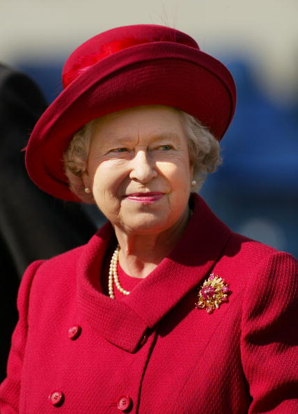 "Queen Elizabeth smiles May 18, 2002 after presenting a trophy for the ""best turned out trooper"" to a Household Cavalry soldier at The Royal Windsor Horse Show at Windsor Great Park, England. (Photo by Sion Touhig/Getty Images)"
