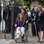 An injured woman arrives at the service in a wheelchair Photo C REUTERS