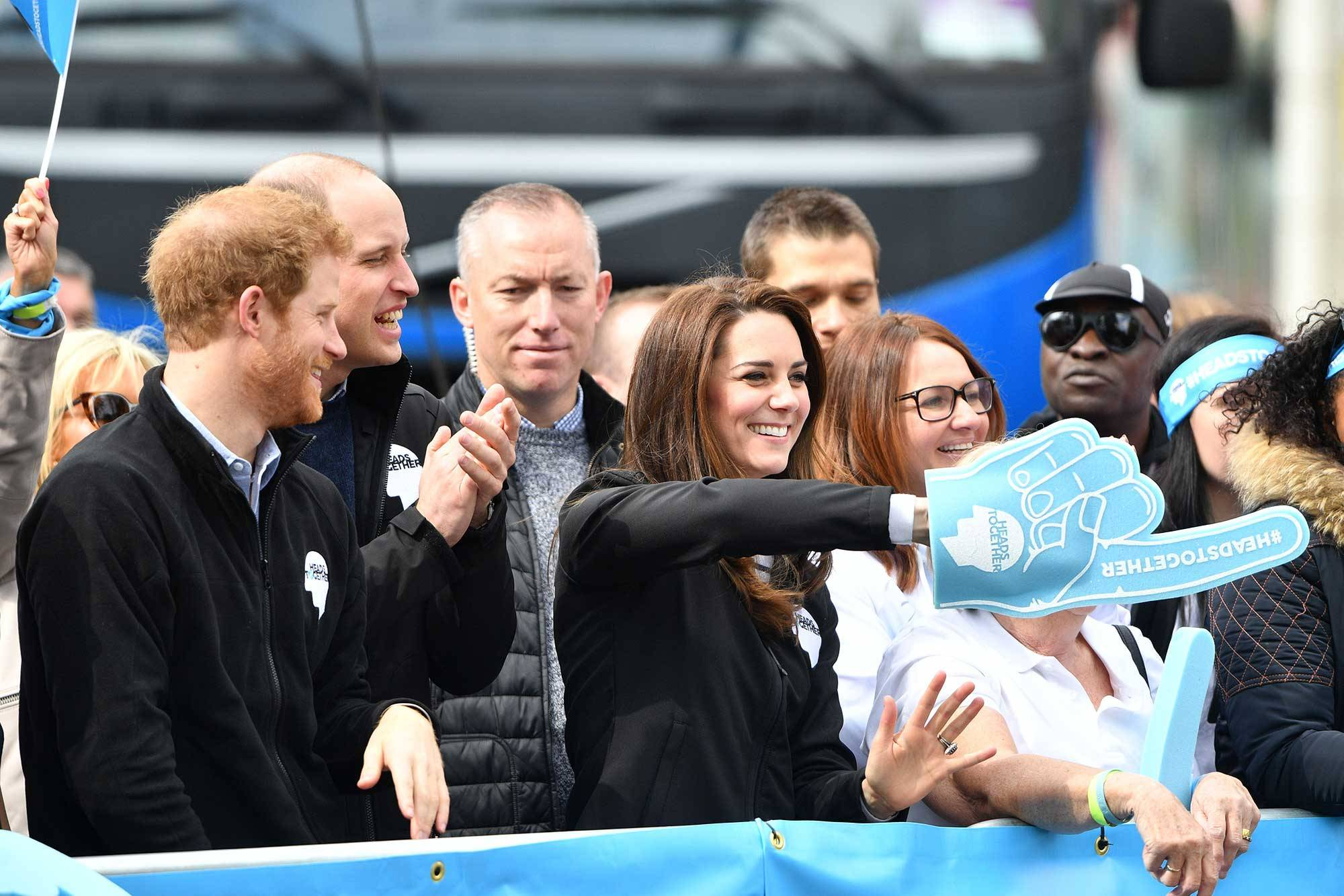 Harry and Kate took turns waving a giant Heads Together foam hand with pointing finger as runners did a double-take when they recognized them Photo (C) GETTY IMAGES