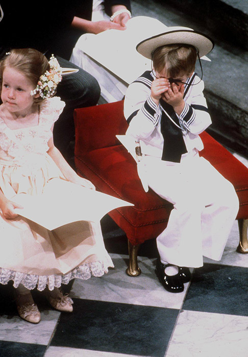 Prince William looked a little bored while waiting for the bride to walk down the aisle, and hilariously hid his face using the string on his straw hat. Sitting on the edge of a lavish red velvet chair, he also showed off patent black shoes with white socks, completing the traditional look. Photo: © Rex