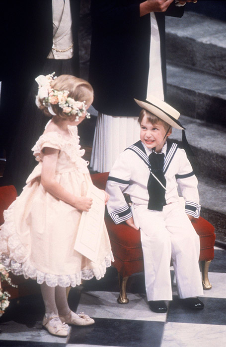 Prince William looked simply adorable in a sailor outfit, complete with a navy blue neckerchief and a matching straw hat, for the wedding of Prince Andrew and Sarah Ferguson in 1986. The little Prince pulled faces at a bridesmaid as they waited for the ceremony to start together. Photo: © Rex