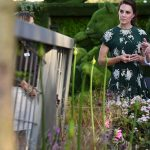 A merry Kate laughed with the men as she displayed her trim figure in a floral print dress which was fitting of the occasion