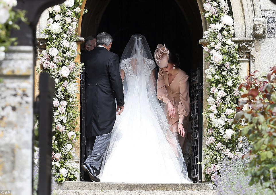 Kate, Duchess of Cambridge, right, arranges the train of her sister of her sister Pippa Middleton as she arrives with her father Michael Middleton for her wedding Photo (C) GETTY IMAGES