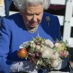 The monarch who donned white gloves was presenting with a beautiful bouquet of flowers during her tour of the grounds