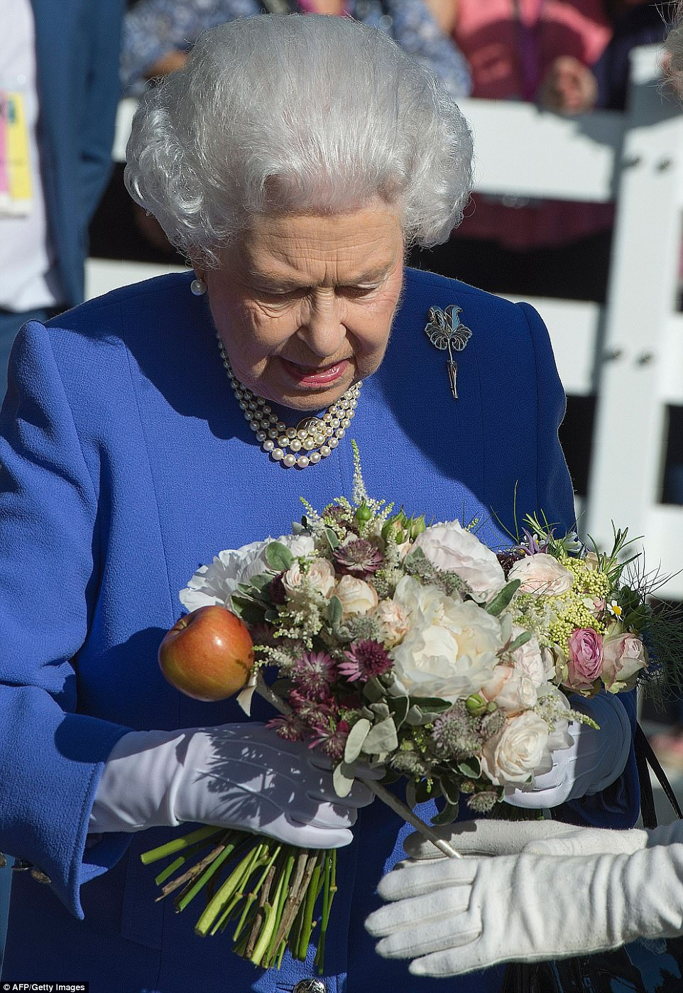 The monarch, who donned white gloves, was presenting with a beautiful bouquet of flowers during her tour of the grounds