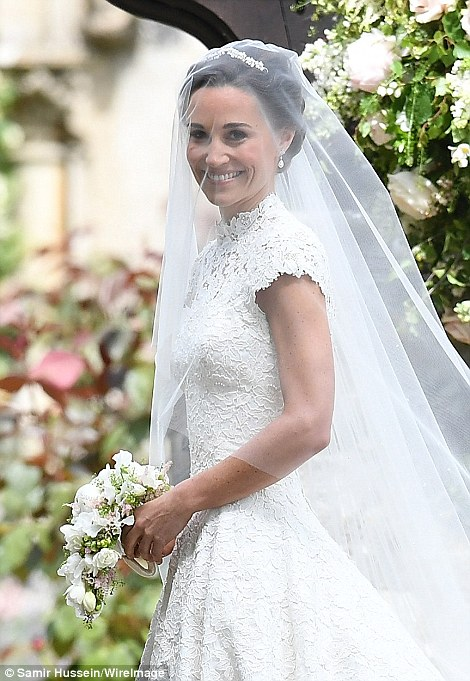 she arrived at the church armed with a small bouquet of white and peach wild flowers Photo (C) GETTY IMAGES