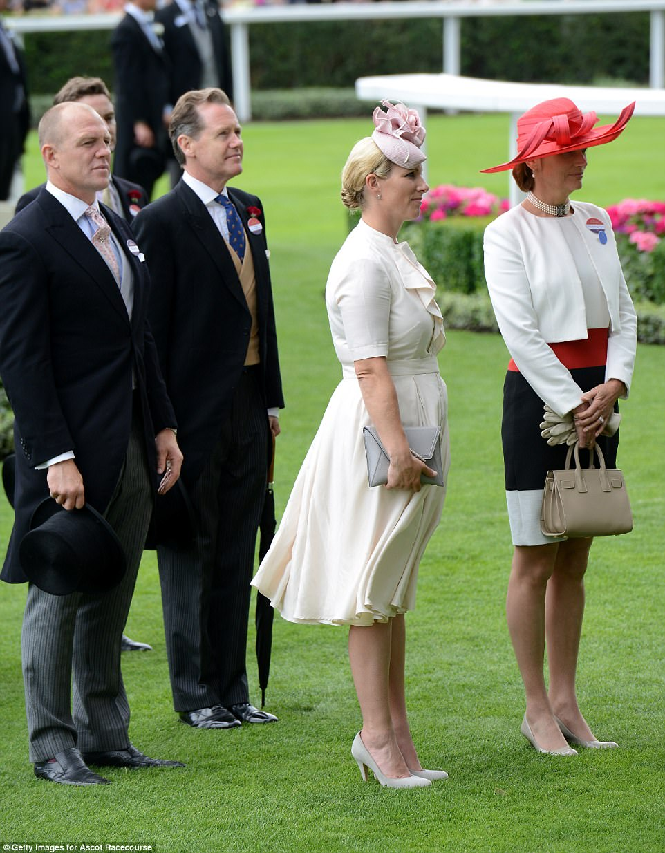 Mike Tindall and his wife Zara stand to attention as they wait the arrival of the Queen in the Parade Ring
