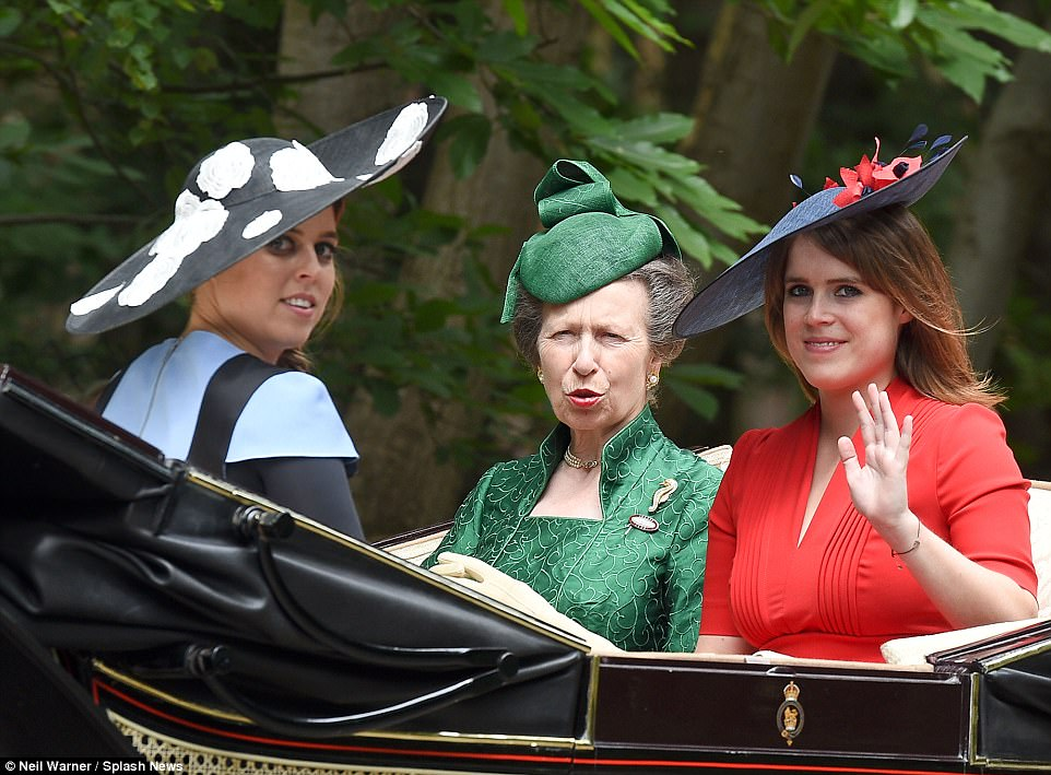 Princess Eugenie waves to the crowds as she travels by carriage with her sister and aunt Princess Anne