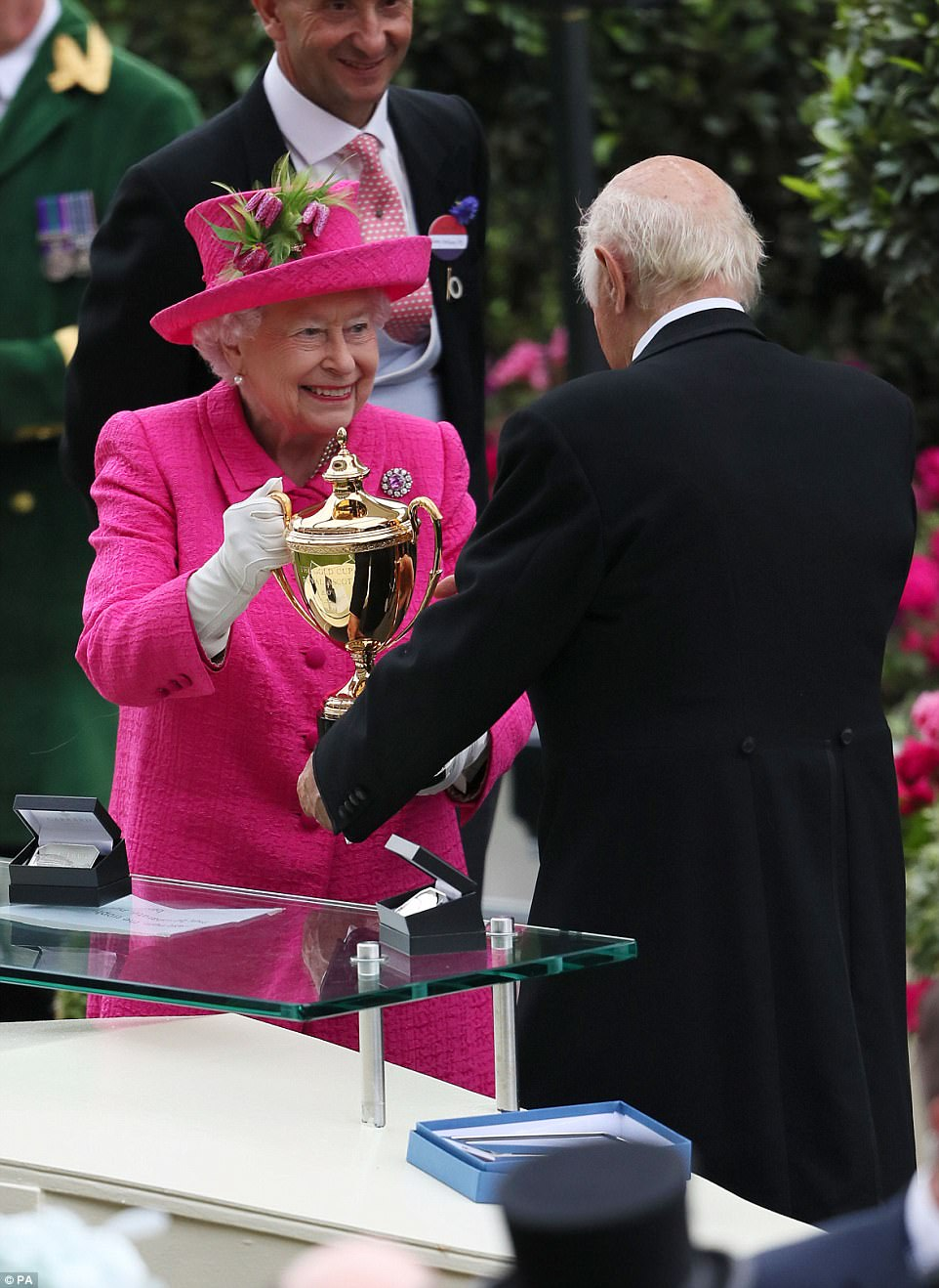 The Queen looks delighted as she holds the trophy to be presented to the owner of the Gold Cup's winning horse, Big Orange