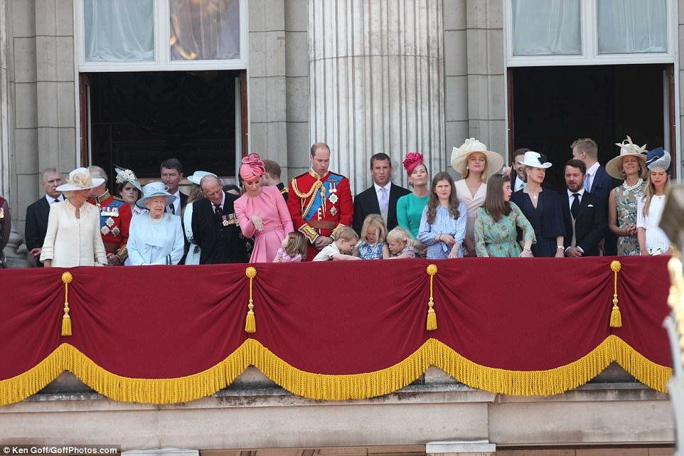 The young Royals, towards the centre of the balcony, seem to preoccupied with something on the floor as their family gathered on the balcony