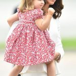 1 The Duchess of Cambridge carried her two year old daughter from the plane and down the steps left. Charlotte was looking adorable in a red and white floral patterned dress