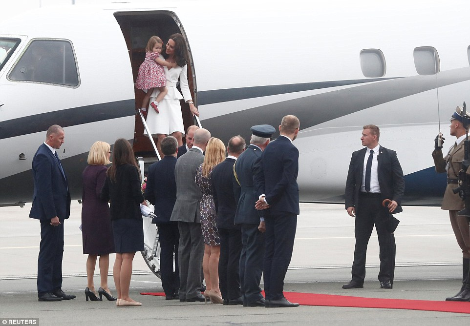His royal shyness! Tearful Prince George needs a little encouragement from Dad as Kate and William arrive in Warsaw - but little sister Charlotte is all smiles