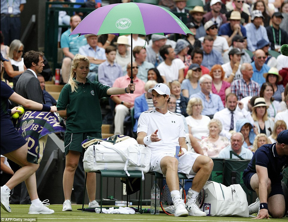Andy Murray is sheltered from the rain during a break in play against Alexander Bublik who represents Kazakhstan