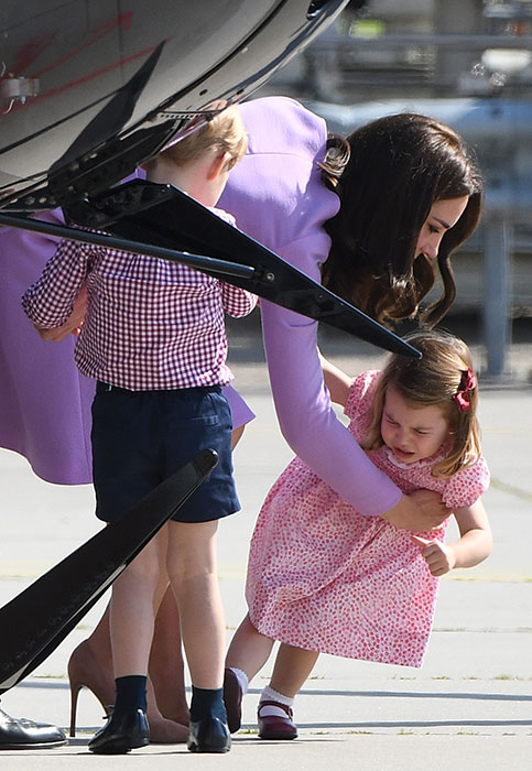 Dressed in a chic lilac dress, Kate appeared to struggle as she picked up her little girl. Photo (C) GETTY IMAGES