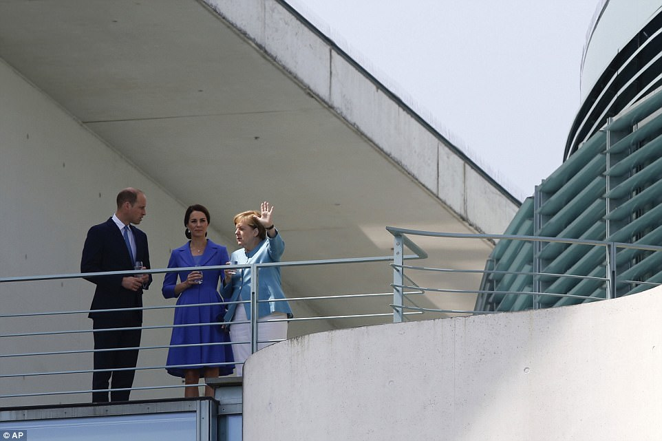 German Chancellor Angela Merkel, right, gestures as she gives William and Kate the first guided tour of their visit to Berlin