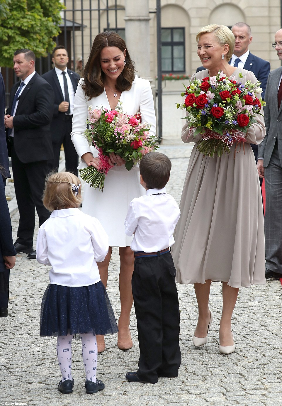 Kate and First Lady Agata Kornhauser-Duda were presented with bouquets by two young wellwishers outside the presidential palace in Warsaw