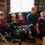 Prince Harry meets Oliver Rooney left who has Wolf Hirschhorn Syndrome with his family who are receiving a garden make over from WellChild at their home in Bramley during an official visit to