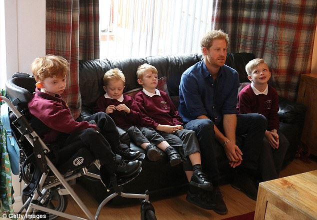 Prince Harry meets Oliver Rooney (left) who has Wolf Hirschhorn Syndrome with his family who are receiving a garden make over from WellChild at their home in Bramley during an official visit to