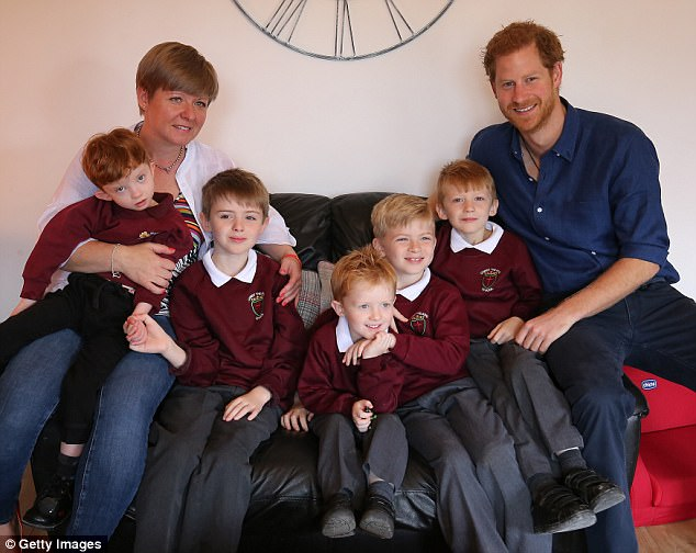 Prince Harry meets Oliver Rooney (left) who has Wolf Hirschhorn Syndrome with mum Elizabeth (left) and brothers Samuel, Jack, Joseph and Thomas who are receiving a garden make over from WellChil