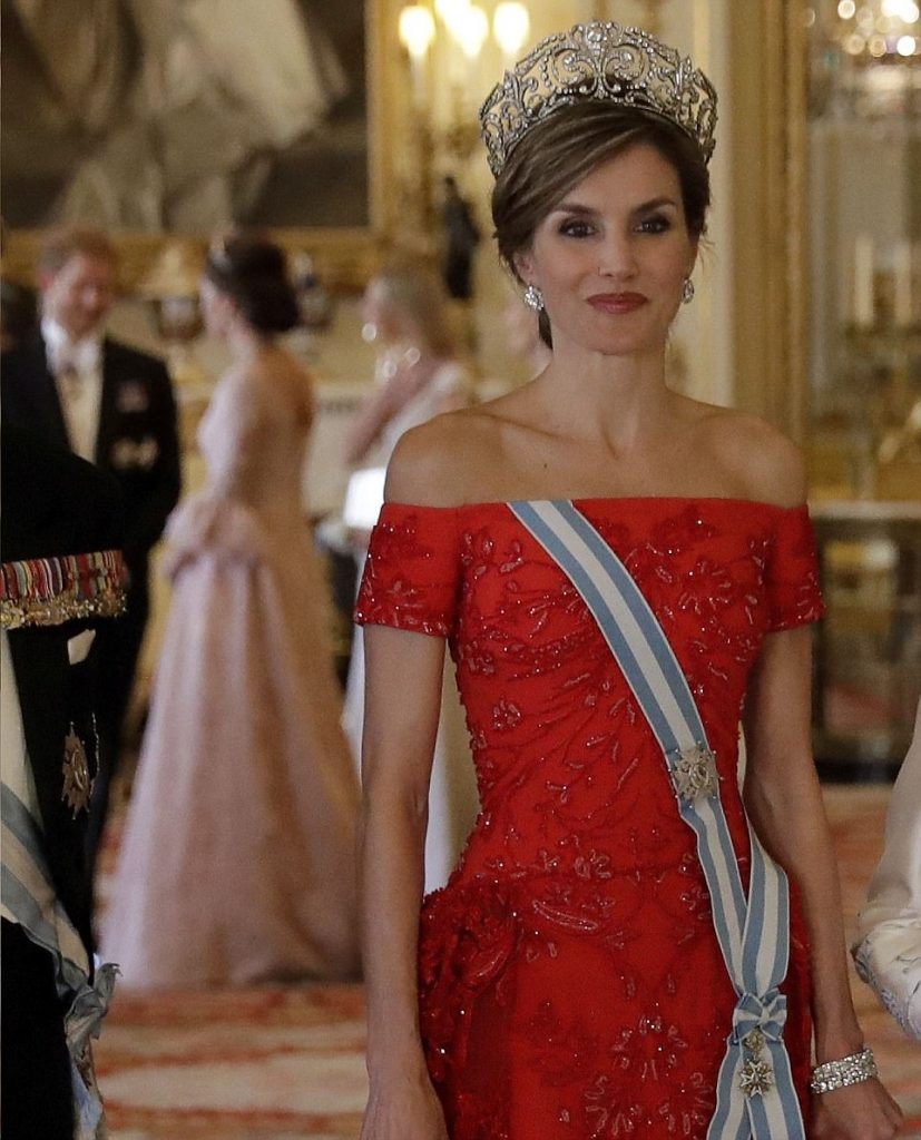 Queen Letizia stunned in her countrys national colour while Kate looked chic in pink as she chatted to Prince Harry in the background