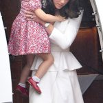 The Duchess of Cambridge carried her two year old daughter from the plane and down the steps left. Charlotte was looking adorable in a red and white floral patterned dress