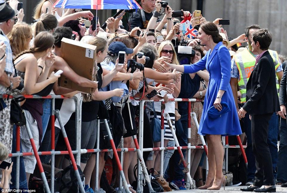The Duchess of Cambridge greets spaectators near Berlin's most iconic landmark the Brandenburg Gate