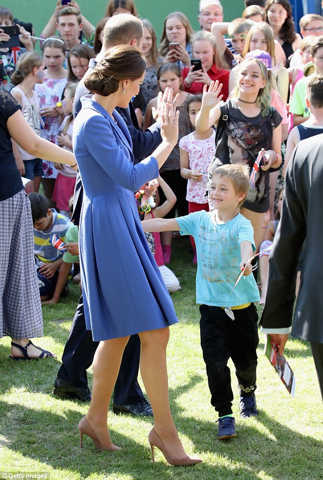 The Duchess of Cambridge yesterday doled out hugs to children as she paid a visit to a charity that supports youngsters from disadvantaged backgrounds