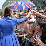 The Duchess shakes hands with fans who shielded themselves from the afternoon sun with Union Jack umbrellas