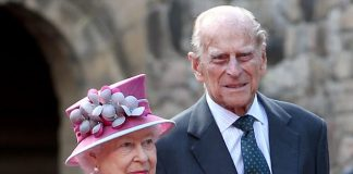The Queen dressed in a fuchsia coat and matching hat with Prince Philip at the castle