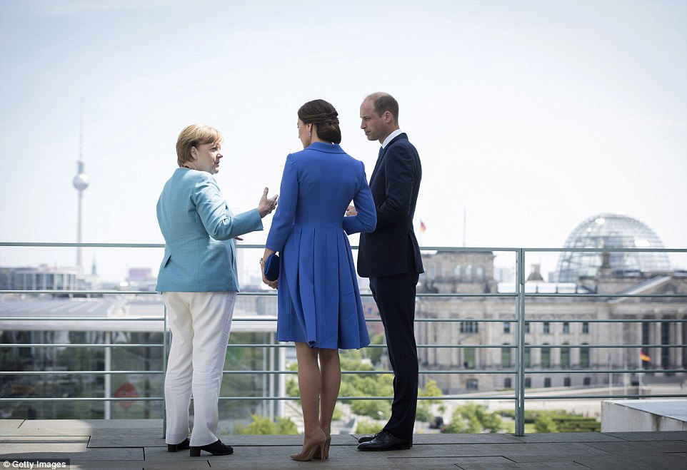 The royals admire the view as Angela Merkel shows them around the Federal Chancellery in Berlin