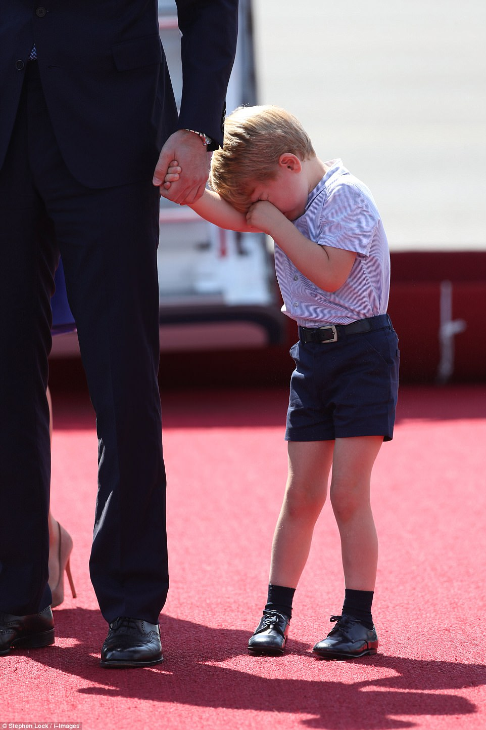 The young prince appeared to be feeling sleepy and was seen rubbing his eyes as his father Prince William greeted officials in Germany