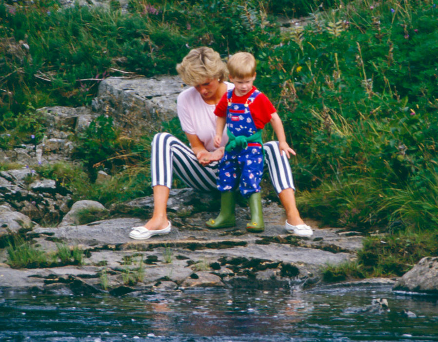 Diana, Princess of Wales, and Prince Harry play on the banks of the River Dee, near Balmoral Castle during a Summer vacation. August 18, 1987 Photo (C) UK PRESS VIA GETTY IMAGES