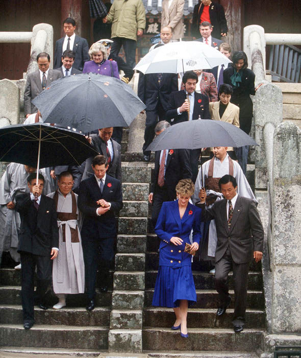 Getty Images The Prince and Princess of Wales are sheltered by umbrellas during a visit to the Pulguska Temple in Korea, 1992 Photo (C) GETTY