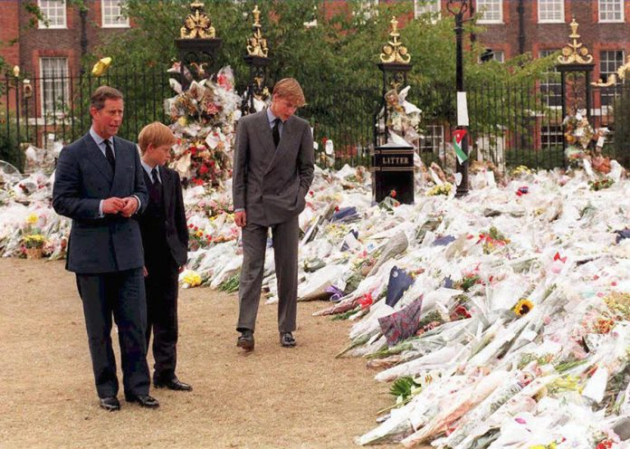 Prince Charles and sons Princes William and Harry take in the sea of floral tributes to their mother, Diana, Princess of Wales, at Kensington Palace, her former London residence in 1997. Photo (C) GETTY