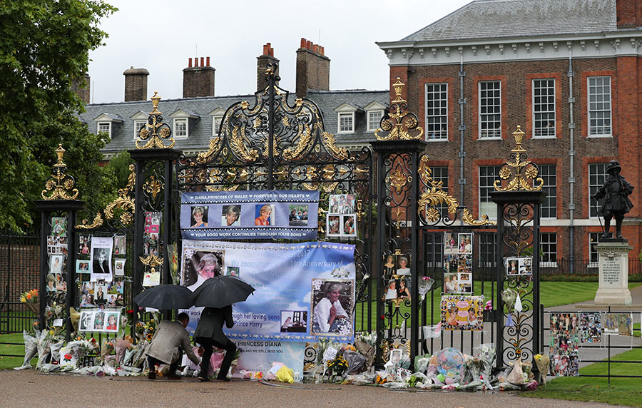 Prince William, Duke of Cambridge and Prince Harry look upon flowers, photos and other souvenirs left as a tribute to Princess Diana near The Sunken Garden at Kensington Palace. Photo (C) PA