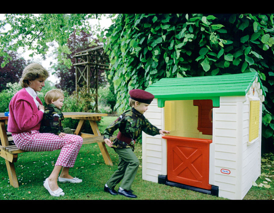 Princess Diana with her sons Prince William and Prince Harry playing with a playhouse in the garden of their home. July 18th, 1986 Photo (C) GETTY IMAGES