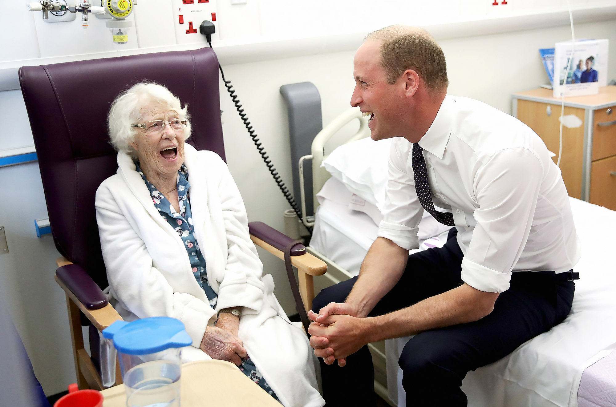 LIVERPOOL, ENGLAND - SEPTEMBER 14: Prince William, Duke of Cambridge shares a joke with patient Theresa Jones in the Frailty unit during a visit to Aintree University Hospital on September 14, 2017 in Liverpool, England. The Duke visited Aintree University Hospital to formally open the new Urgent Care and Trauma Centre (UCAT). This new unit, serving a catchment area of 2.3m residents in the North West, opened in January 2017 following a £35m redevelopment. (Photo by Chris Jackson/Getty Images)