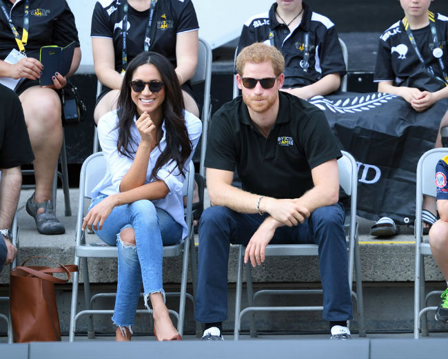 Meghan kept a protective guard with her legs crossed during her debut public appearance with Harry Photo (C) GETTY