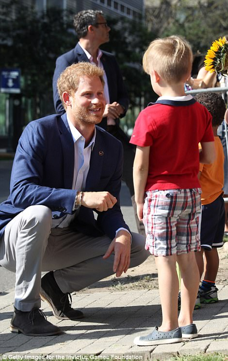 The 33-year-old prince dressed in a dark blue blazer, a light blue shirt and khaki-colored pants was seen smiling as he shook hands, bent down to greet children and even pet a dog