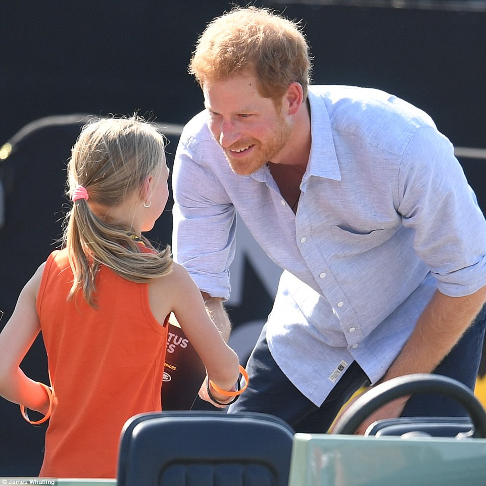 Prince Harry shakes Daimyb Gommers's hand after she took him for a spin in a miniature Land Rover