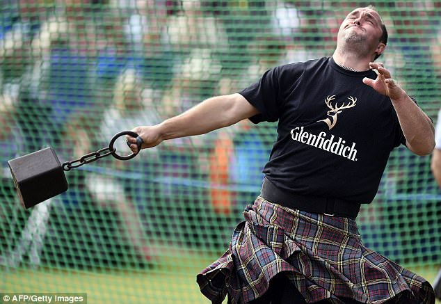 The Queen was just one of thousands of spectators who turned out for the historic gathering. Pictured A competitor takes part in a weight throw