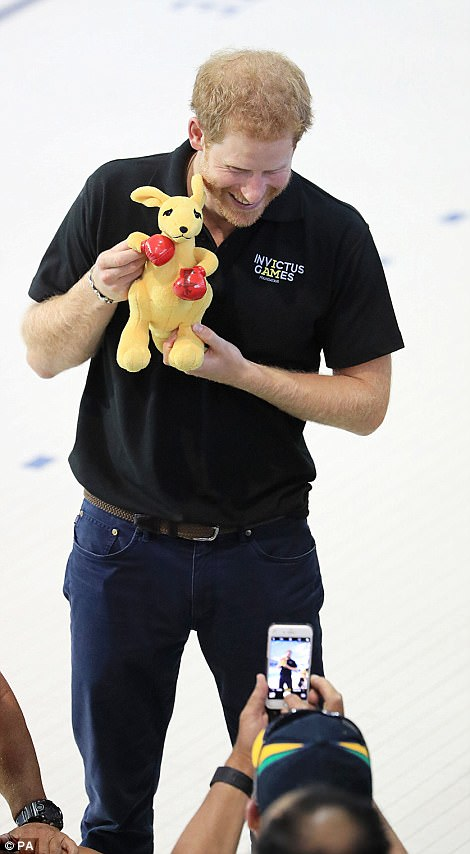 The handsome man smiled as he posed with a stuffed toy kangaroo for a fan's photo during the event, sporting a black shirt with the Invictus Games logo