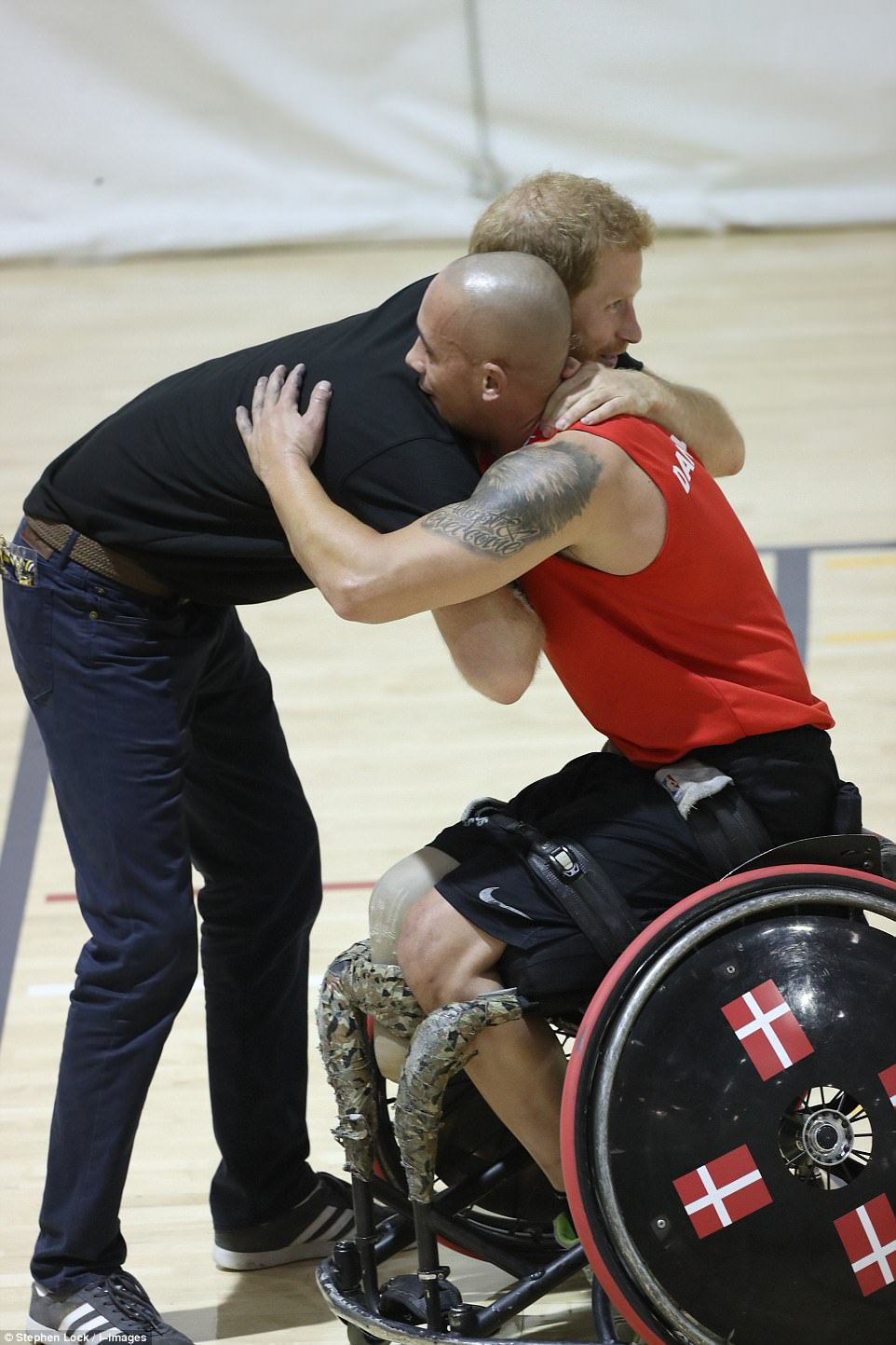The prince is counting down to the opening of the Invictus Games - and went to a training session where he hugged one of the wheelchair athletes taking part