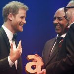 Prince Harry receives a posthumous Legacy award on behalf of his mother Diana Princess of Wales from Ian Walker right and Julian La Bastide. Credit PA
