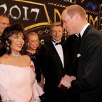 Dame Joan Collins wearing a light pink dress and elaborate diamond jewellery shared a warm exchange with Prince William