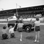 Queen Elizabeth II and the Duke of Edinburgh pass a group of youngsters raising their cups whilst driving in an open top vehicle around Hove Stadium East Sussex.