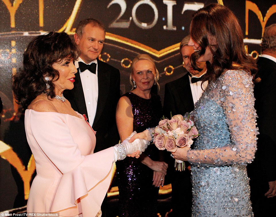 The Dame and the Duchess Joan Collins and Kate shake hands after the show, Kate's bouquet of roses almost matches Joan's dress perfectly