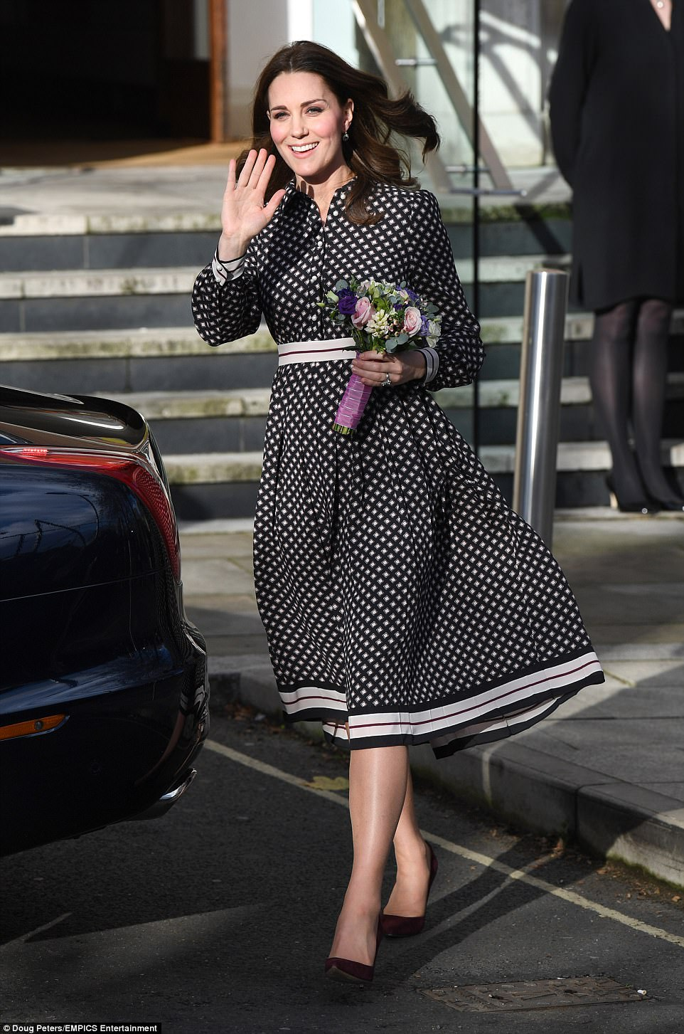 The Duchess looked chic in a pleated Kate Spade dress, which she offset with burgundy accessories for the occasion
