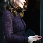 The Duchess looked elegant in a recycled purple coat from maternity brand Seraphine and carried a small black clutch bag